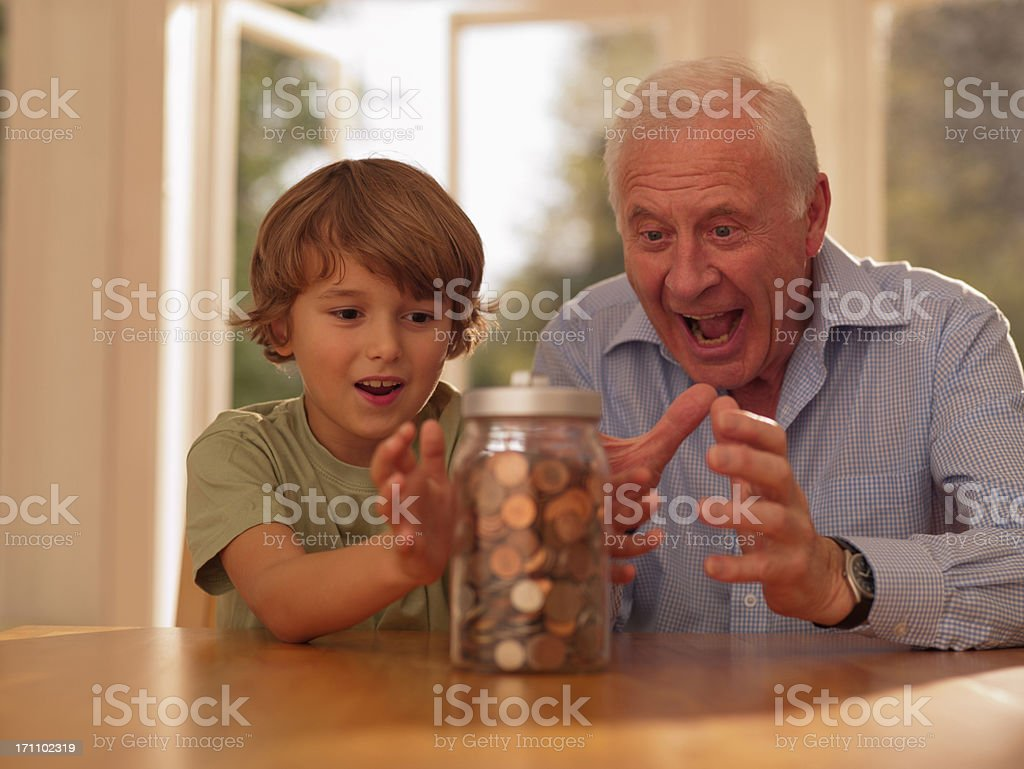 Grandfather and grandson hold at jar full of coins stock photo