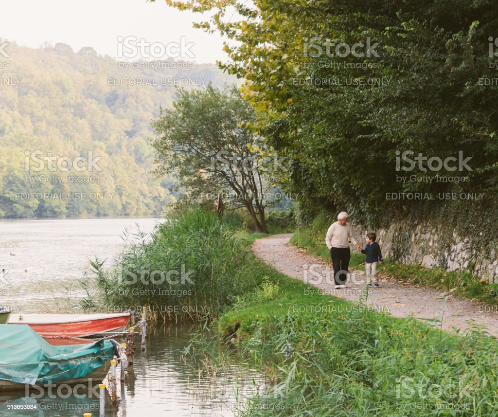 Grandfather and grandson hold hands while walking on a path next to a river in Italy stock photo