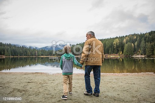Grandfather walking with his grandson on sandy beach toward calm lake on overcast, autumnday.
