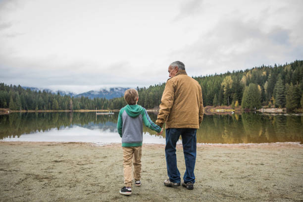 Grandfather and grandson holding hands, walking towards lake. Whistler, Canada