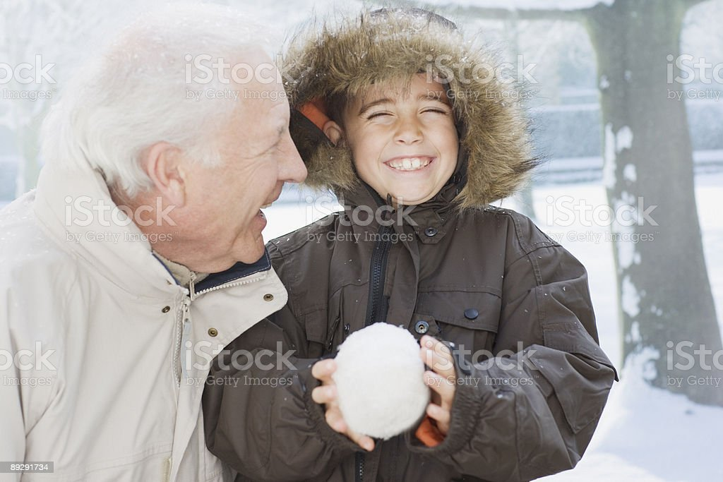 Grandfather and grandson holding snowball stock photo