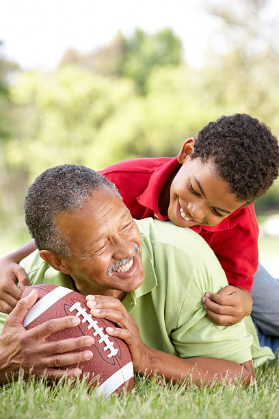 Grandfather and Grandson In Park With American Football stock photo