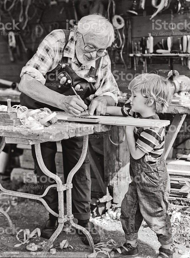 Grandfather and grandson in workshop royalty-free stock photo