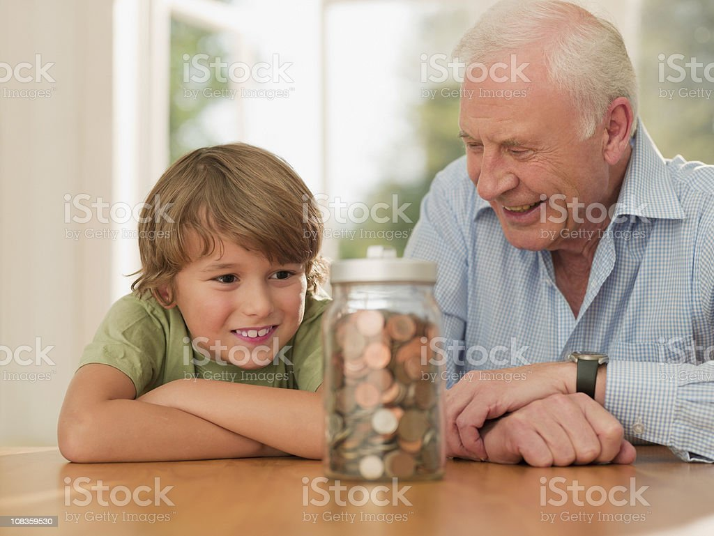 Grandfather and grandson looking at jar full of coins stock photo