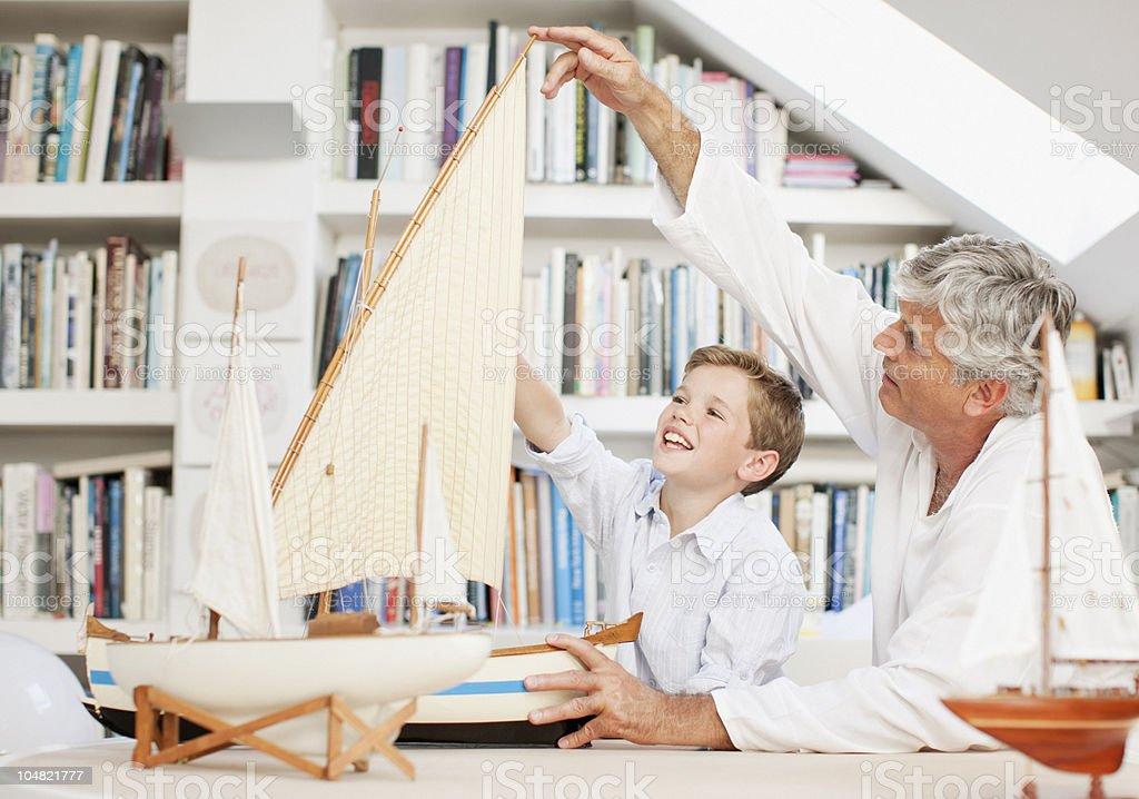 Avô e neto olhando modelo de barcos à vela - foto de acervo