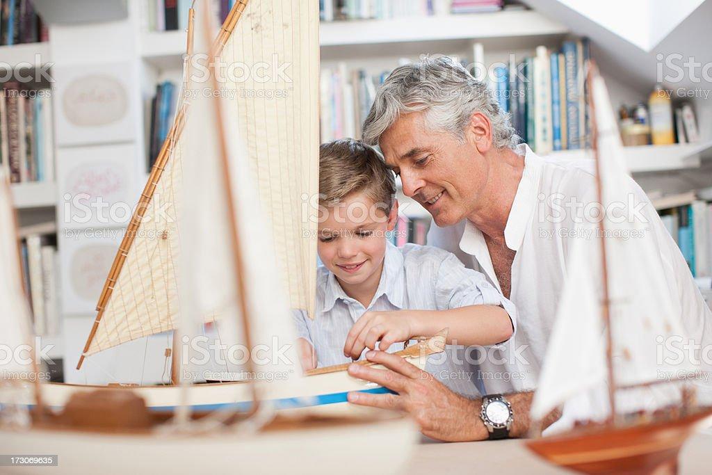 Grandfather and grandson looking at model sailboats stock photo