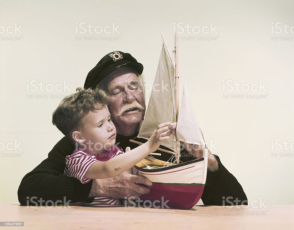 Grandfather and grandson looking at ship model against white background royalty-free stock photo