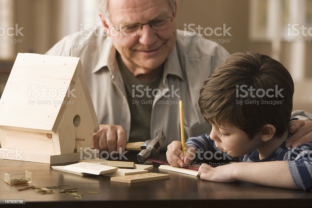 Grandfather and grandson making birdhouse stock photo