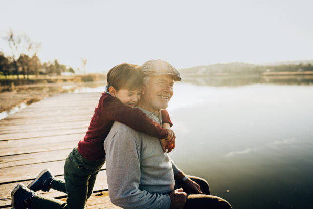 Grandfather and grandson on a lake dock stock photo