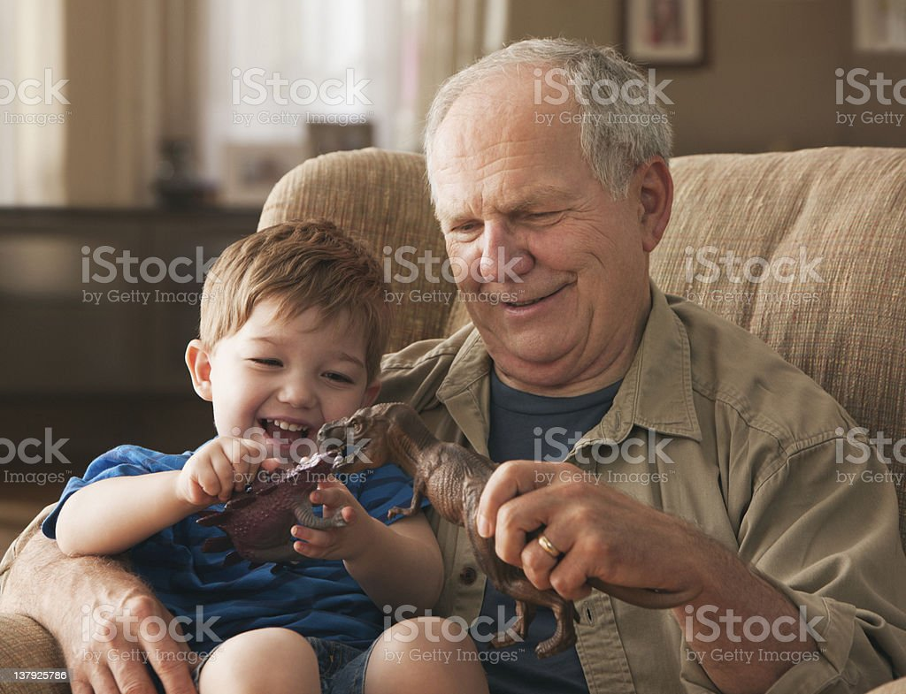 Grandfather and grandson paying with toy dinosaurs stock photo