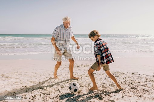 Close up of a grandfather playing with his grandson on the beach