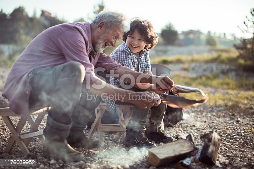 Close up of a grandfather cooking a fish with his grandson over a campfire next to a river