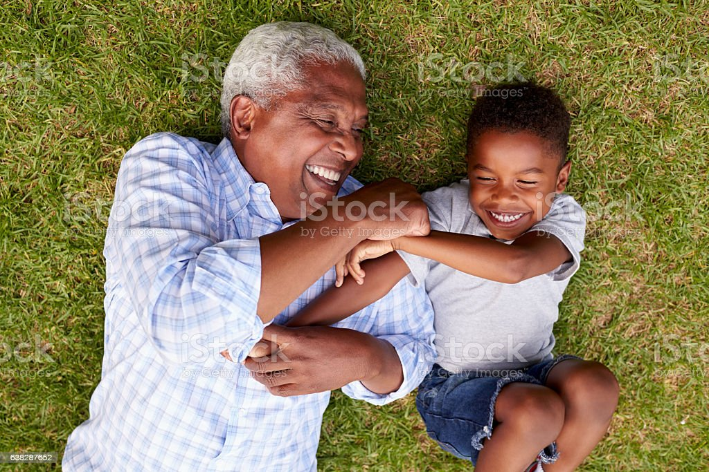Grandfather and grandson play lying on grass, aerial view stock photo
