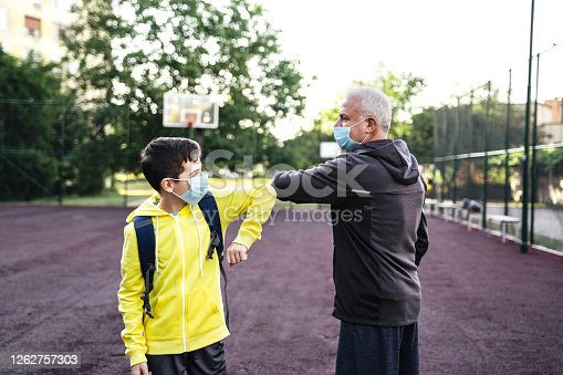 Grandfather And grandson playing basketball during quarantine and wearing face protective mask. Alternative greeting for safety and protection during COVID-19. Coronavirus epidemic. New normal.