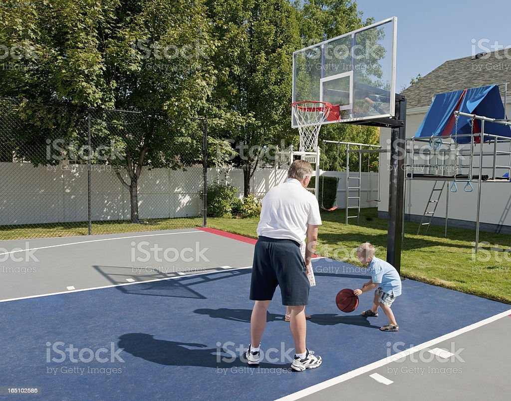 Grandfather And Grandson Playing Basketball stock photo