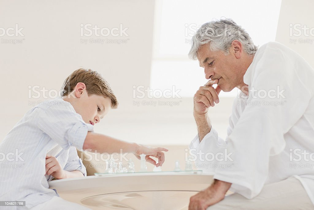 Grandfather and grandson playing chess stock photo