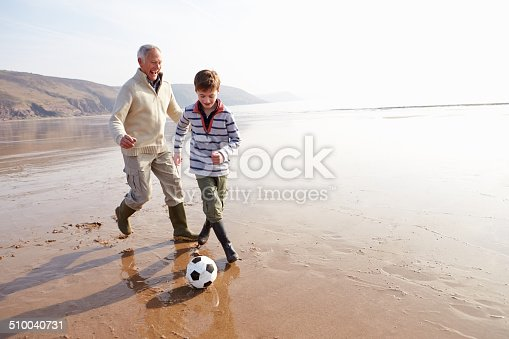 istock Grandfather And Grandson Playing Football On Winter Beach 510040731