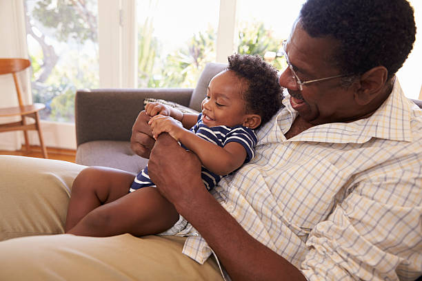 Grandfather And Grandson Playing Game On Sofa At Home stock photo