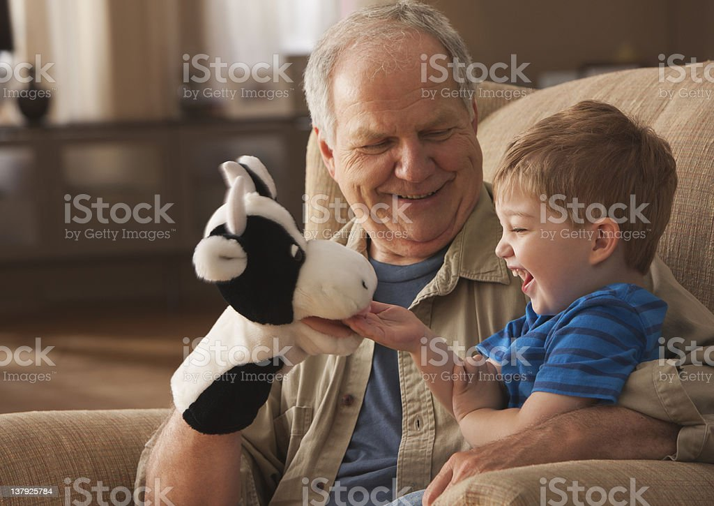 Grandfather and grandson playing with puppets royalty-free stock photo