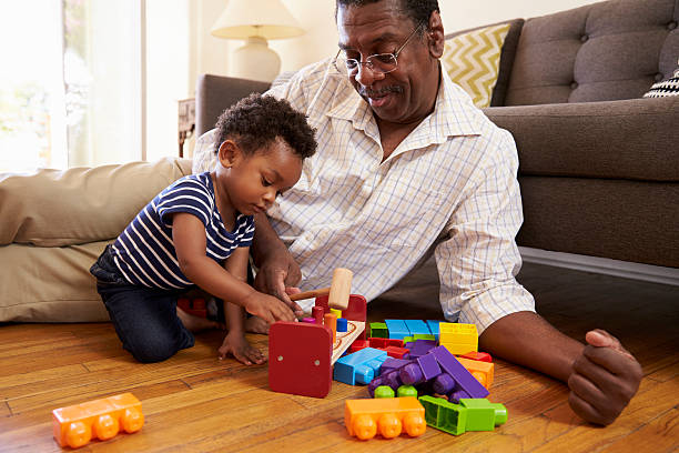 Grandfather And Grandson Playing With Toys On Floor At Home stock photo
