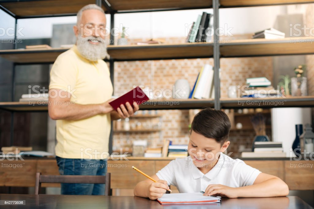 Grandfather and grandson practicing spelling via dictation stock photo