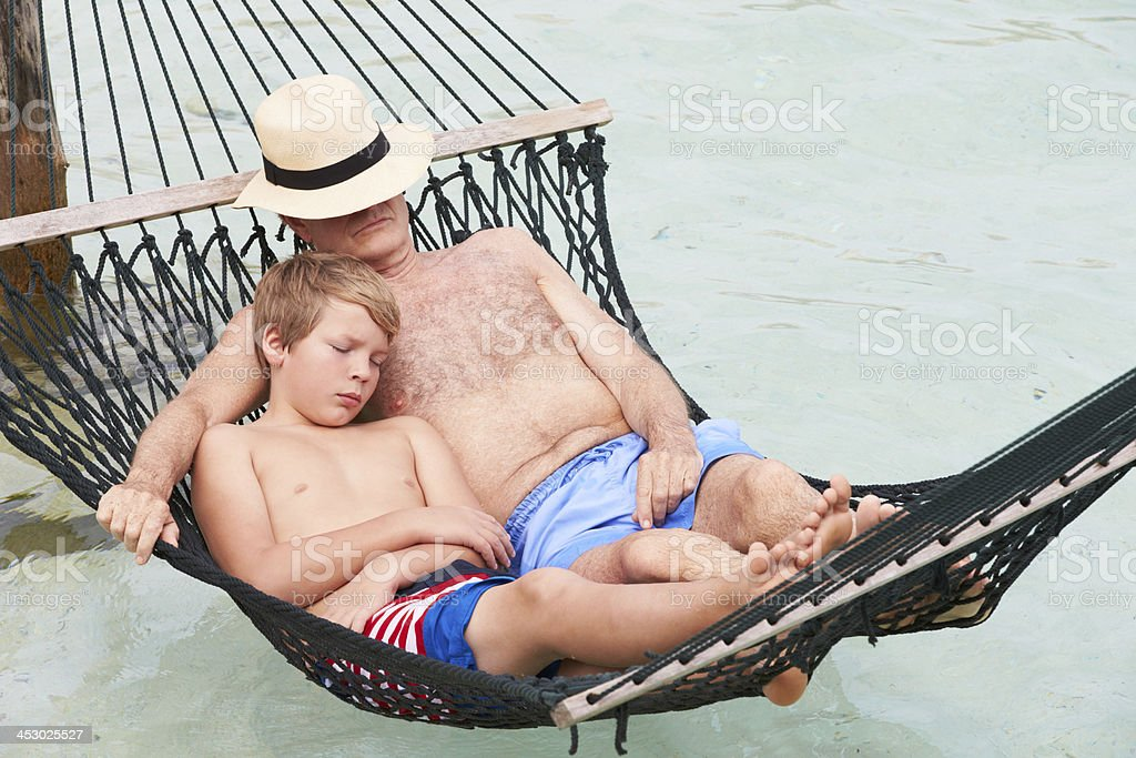 Grandfather And Grandson Relaxing In Beach Hammock royalty-free stock photo
