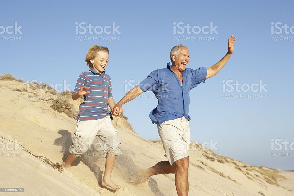 Grandfather And Grandson Running Down Sand Dune royalty-free stock photo