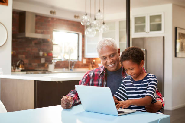 Grandfather And Grandson Sitting Around Table At Home Using Laptop Together stock photo