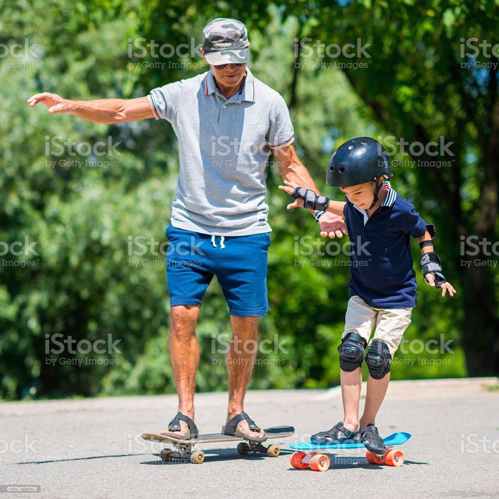 Grandfather and grandson skateboarding together - foto de acervo