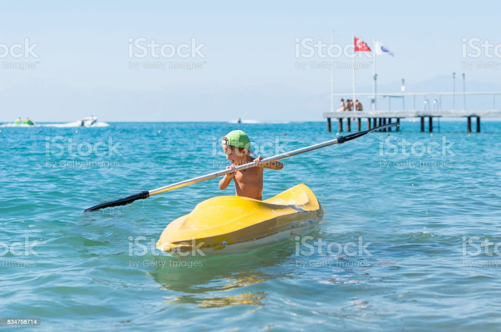 Grandfather and grandson smiling little baby boy in green baseball cap kayaking at tropical ocean sea in the day time. Positive human emotions, feelings, joy. Funny cute child making vacations and enjoying summer. Happy family. stock photo