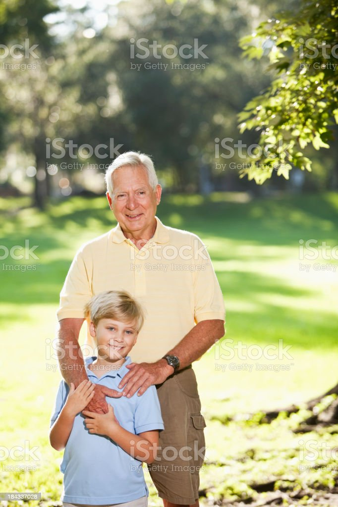 Grandfather and grandson standing together in park stock photo