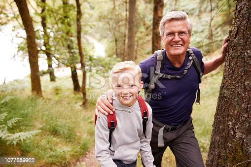 istock Grandfather and grandson taking a break while hiking together in a forest, close up, smiling to camera 1077689922