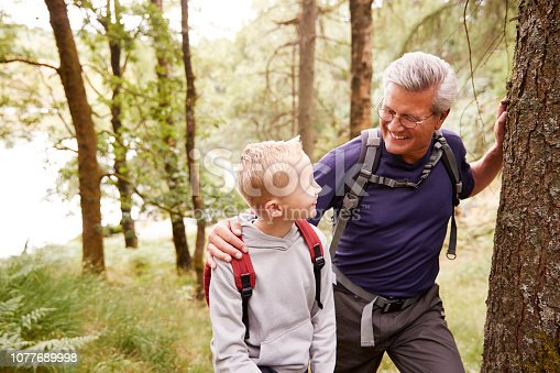 istock Grandfather and grandson taking a break while hiking together in a forest, close up, looking at each other 1077689998