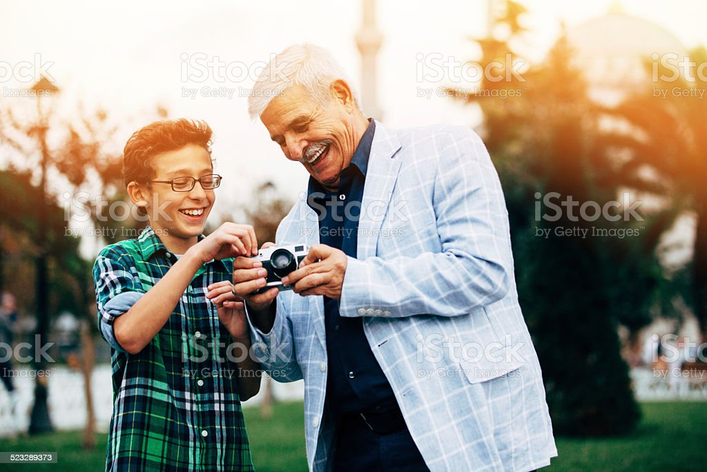 Grandfather And Grandson taking pictures stock photo