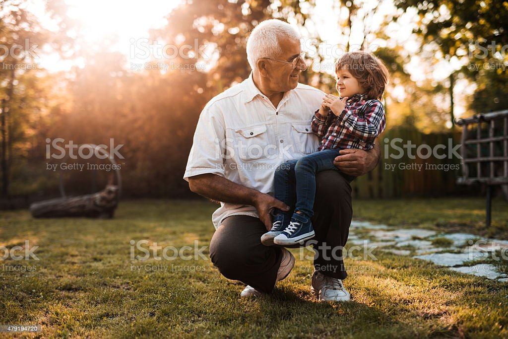 Grandfather and grandson talking to each other at sunset. stock photo