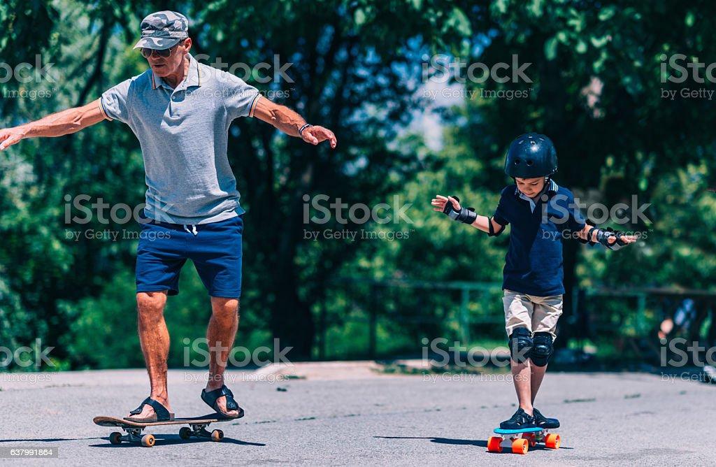 Grandfather and grandson trying skateboards - foto de acervo