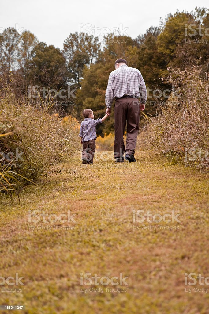 Grandfather and grandson walking away royalty-free stock photo