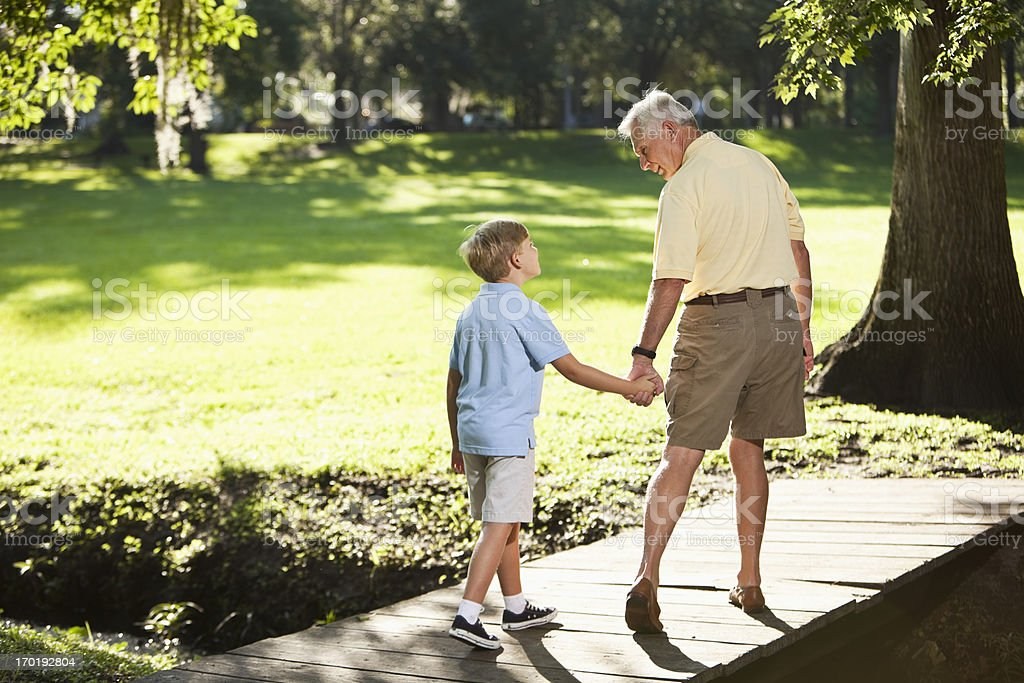 Grandfather and grandson walking in park stock photo