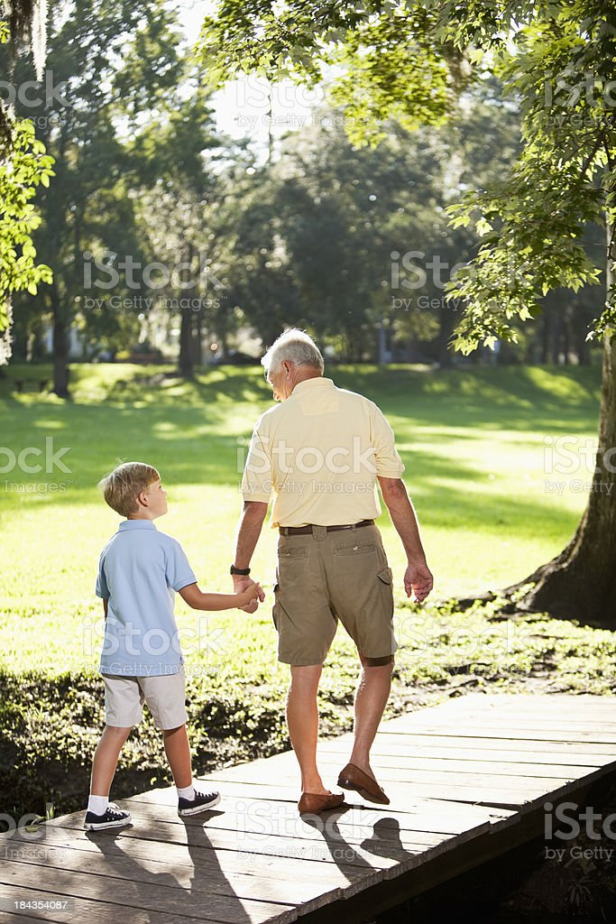 Grandfather and grandson walking in park royalty-free stock photo