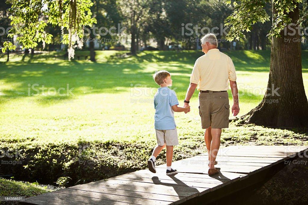 Abuelo y nieto caminando en el parque - foto de stock