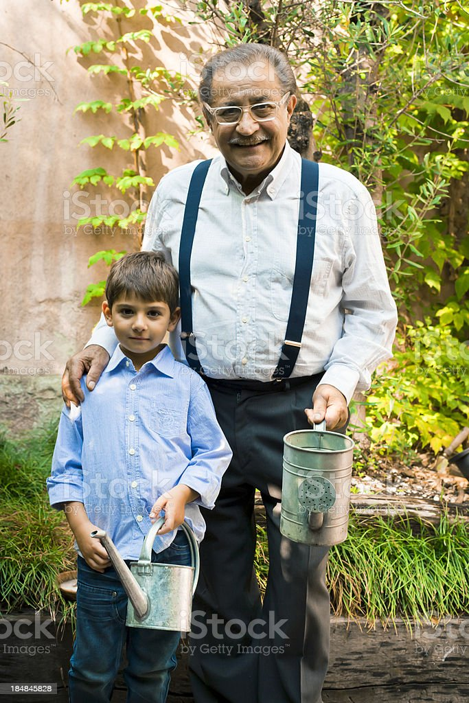 Grandfather and grandson watering plants in patio royalty-free stock photo