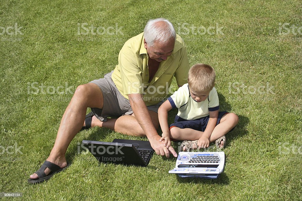Grandfather and grandson working on laptops royalty-free stock photo