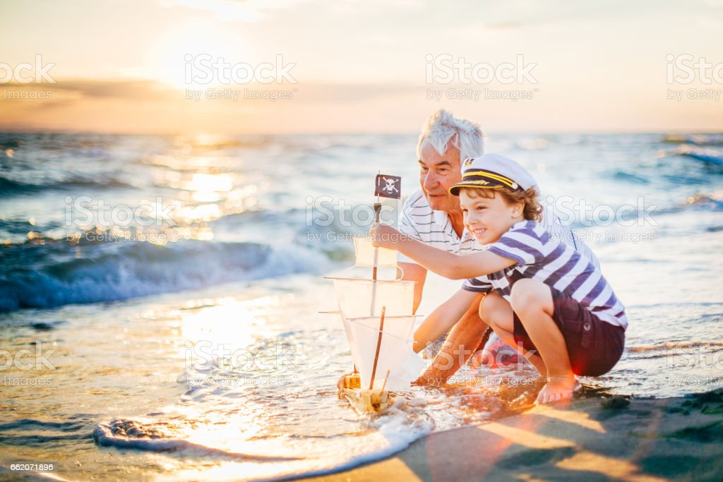Grand-père et son petit-fils s'amuser sur la plage - Photo