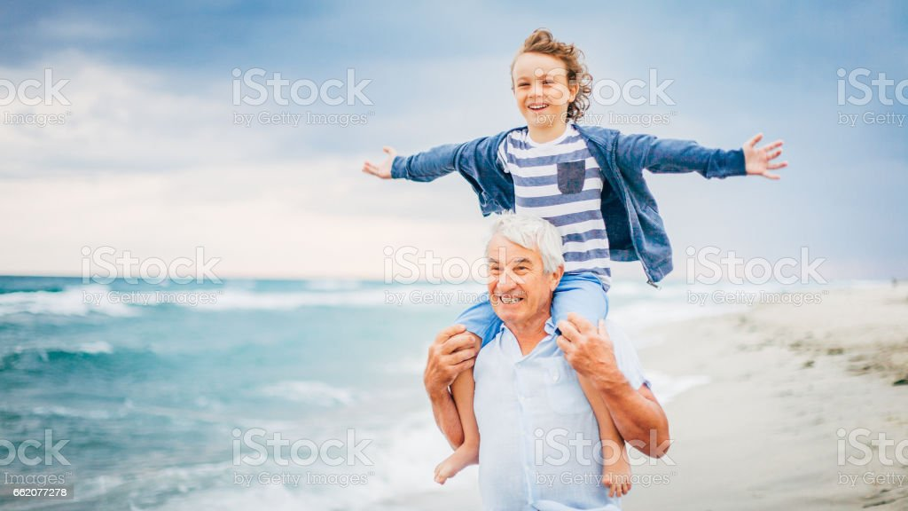 Grandfather and his grandson having fun on the beach stock photo