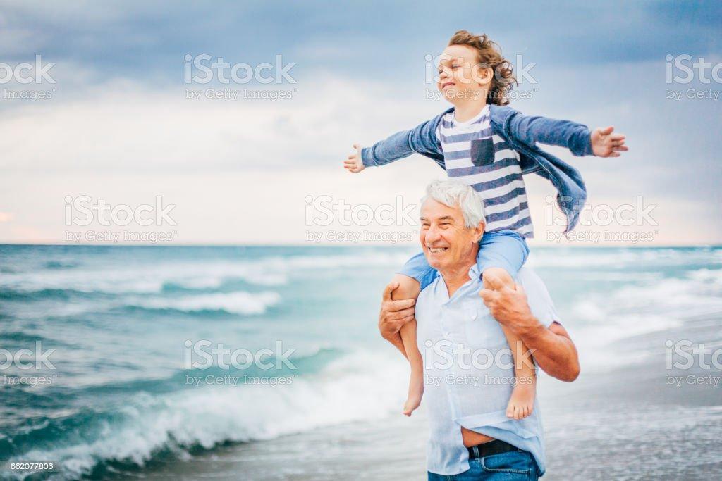 Abuelo y su nieto que se divierten en la playa - foto de stock