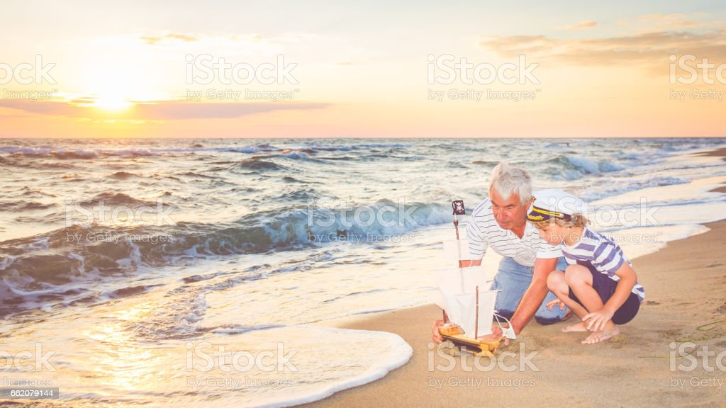 Grandfather and his grandson having fun on the beach royalty-free stock photo