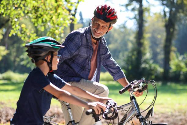 Großvater und sein Enkel im Gespräch auf einer Radtour in der Natur – Foto
