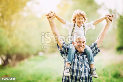 Grandpa enjoying a walk with his grandson, carrying him on his shoulders. Both are very happy, enjoying their time together. Copy space available.