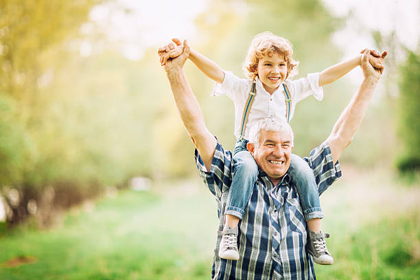 Grandfather and his grandson walking outdoors stock photo