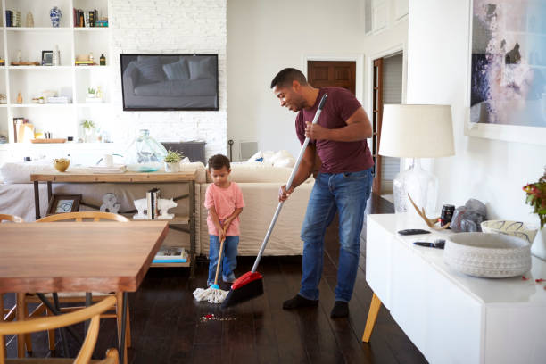grandfather and his three year old grandson mopping and sweeping the dining room floor, full length - sweeping stock pictures, royalty-free photos & images